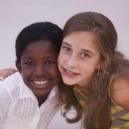 An Ethiopian adoptee and her sister smile and hug.