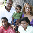 Birth parents and adoptive parents smile with son.
