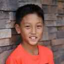 A teen boy who was adopted from Korea as an infant smiles against a stone wall.