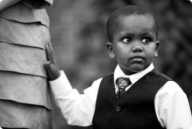 Lisa's son stands with his hand on his mother's dress and looking to the left. He is of African descent and dressed in a tie, vest and button up shirt. Photo credit Kara Pennington Photography.