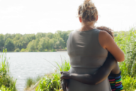 A white mother hugs her African American daughter while looking at a lake. The photo is taken from behind.