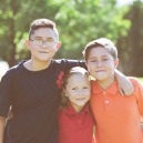 Three siblings in foster care smile in the part with their arms wrapped around each other's shoulders.