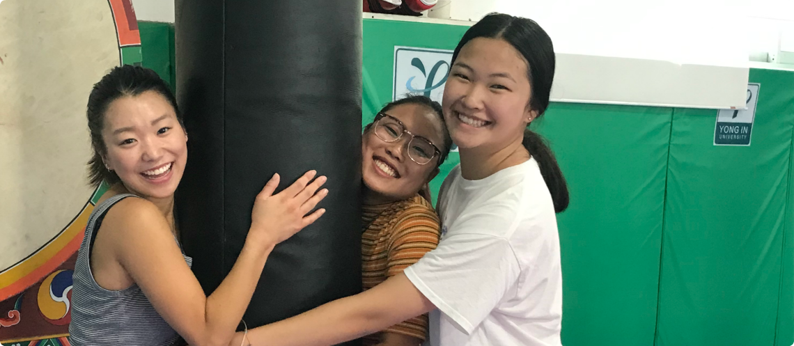 Three Korean adoptees hug a punching bag and get goofy while traveling in South Korea.