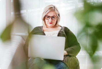 A 35-year-old blonde woman sits on her computer looking for her birth mother on Ancestry DNA.