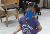 A censored photo of HN as she plays at a table. She waits in Asia for an adoptive family.