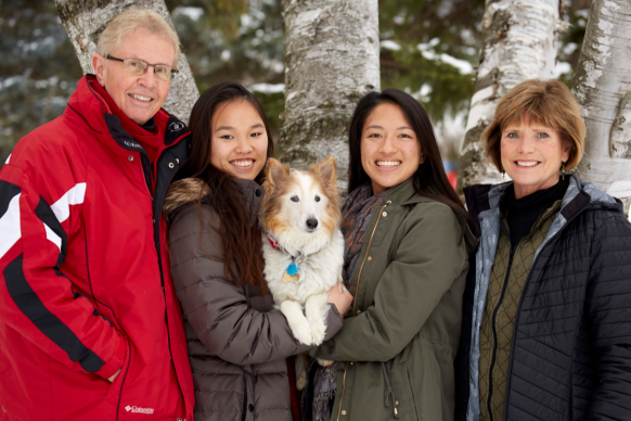 Family with white parents and Asian adopted daughters and dog