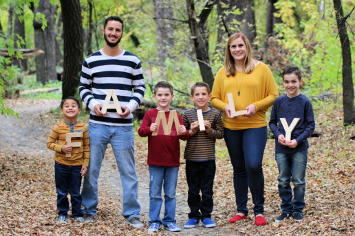 Family with four brothers holds letters spelling out Family