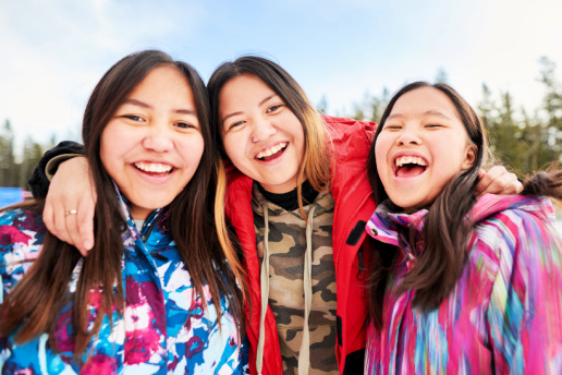 Three Native American girls smile and pose for the camera