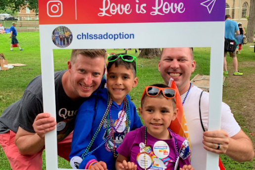 Two dads and their sons pose at Children's Home booth at Pride