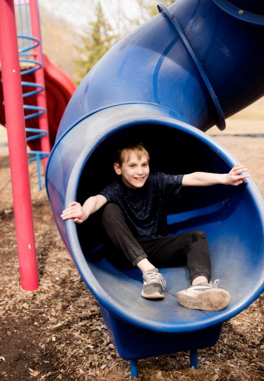 Boy plays on slide at playground