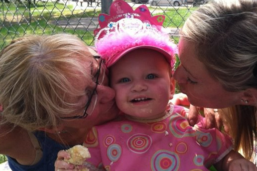 Birth mother and adoptive mother kiss baby's cheeks